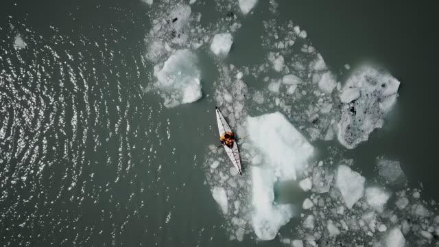 aerial drone: man in kayak sitting in ice filled water near glacier - volume fluid capacity stock videos & royalty-free footage
