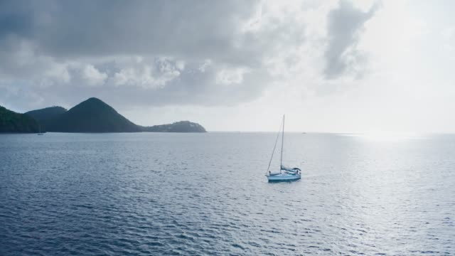 aerial drone moves away from a yacht going to sea and shot of dark wooded mountains and thick clouds (saint lucia) - 船の一部点の映像素材/bロール