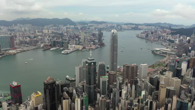 vidéos et rushes de aerial drone movie volant au-dessus des gratte-ciel et de la baie à victoria peak, hong kong - victoria peak