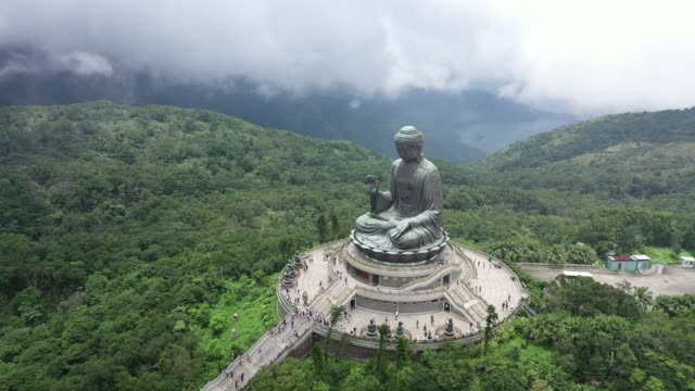 stockvideo's en b-roll-footage met luchtfoto drone film van big bhudda standbeeld in foggy en clouldy day, ngong ping 360, hong kong - monument