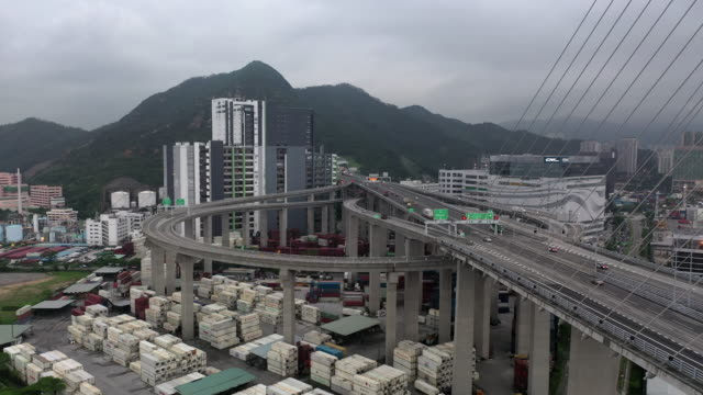 aerial drone movie of traffice car and container ship yard at container terminals and stonecutters bridge, hong kong - bridge built structure stock videos and b-roll footage