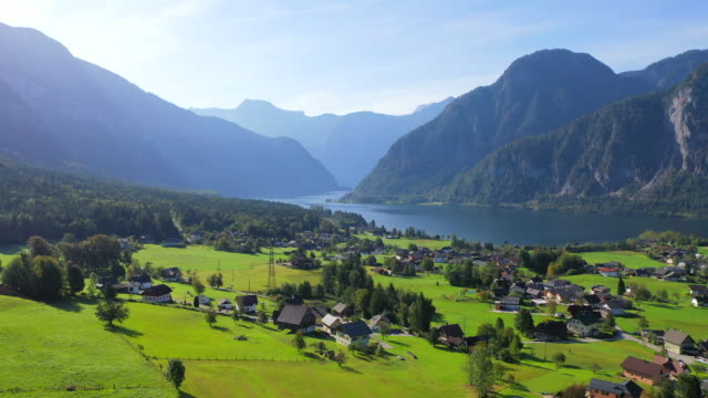 aerial drone movie of village, mountain and lake around hallstatt village, austrian alps, upper austria, europe - valley stock videos & royalty-free footage