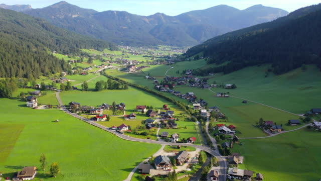 aerial drone movie of village, mountain and lake around hallstatt village, austrian alps, upper austria, europe - austria stock videos & royalty-free footage