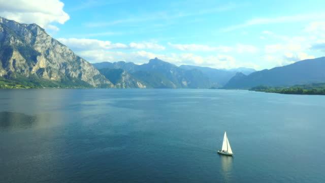 aerial drone movie von yacht auf einem klaren berg und wolfgangseein der österreichischen alpenlandschaft - austria stock-videos und b-roll-filmmaterial
