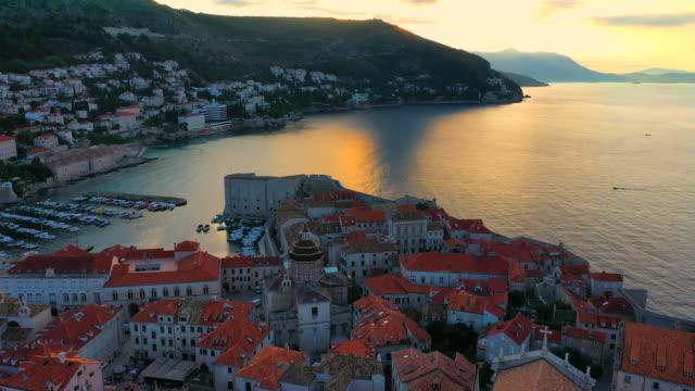 vidéos et rushes de scène de lever de soleil de film de drone aérien de la vieille ville de dubrovnik dans la mer méditerranée, croatie méridionale.  dubrovnik a rejoint la liste du patrimoine mondial de l'unesco. - pierre matériau de construction