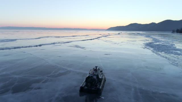 aerial: drone moving along hovercraft floating on frozen lake baikal during sunset - hovercraft stock videos & royalty-free footage