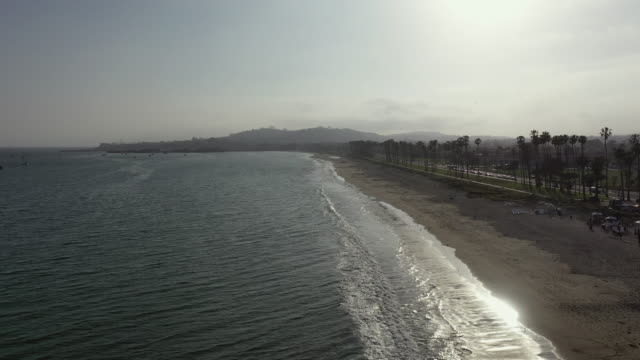 aerial: drone moving along waves splashing on shore at beach in city against sky during morning - santa barbara, california - santa barbara california stock videos & royalty-free footage