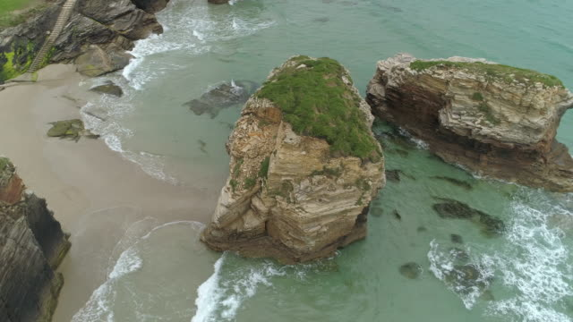 aerial: drone moving around waves splashing on rock formations at as cathedrals beach - playa de las cathedrals, spain - cathedral stock videos & royalty-free footage