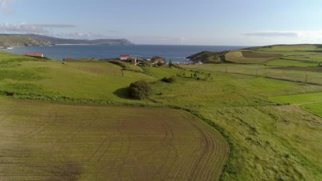 vídeos de stock e filmes b-roll de aerial: drone moving over green farmland approaching coastal village by sea against blue sky on sunny day - galicia, spain - cidade pequena