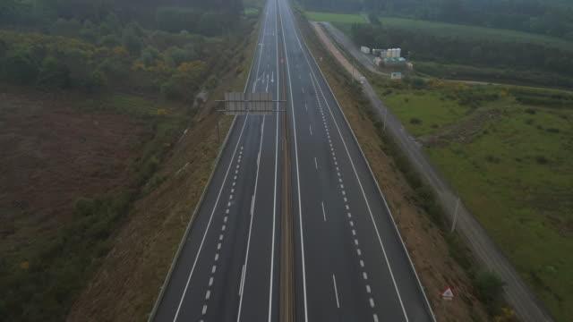 vídeos y material grabado en eventos de stock de aerial: drone moving over highway amidst green trees and field against sky - galicia, spain - galicia