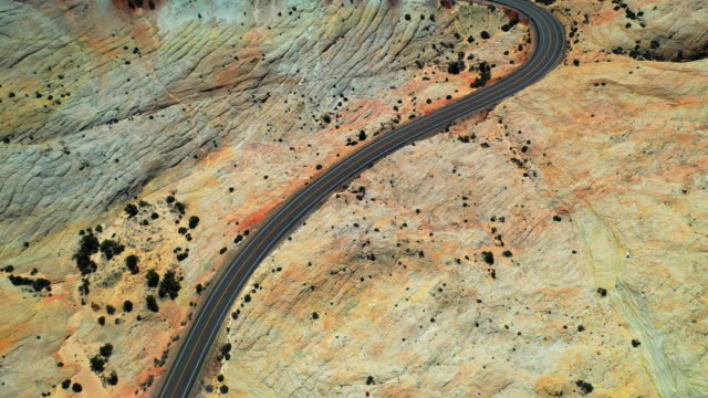 aerial: drone moving over highway at grand staircase-escalante national monument in desert - grand staircase escalante national monument stock-videos und b-roll-filmmaterial