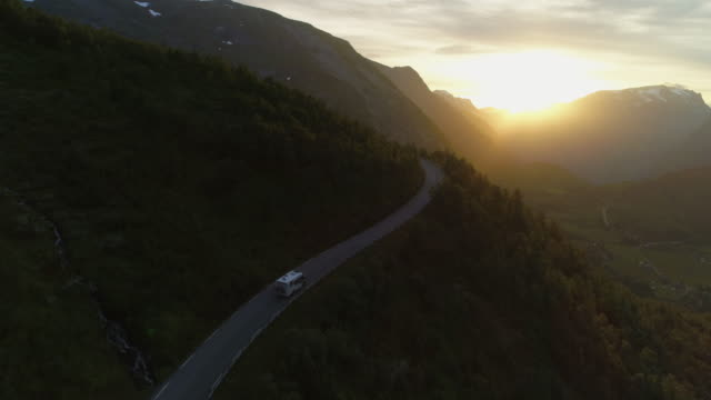 aerial: drone moving over motor home traveling on winding road amidst mountains - geiranger fjord, norway - mountain road stock videos & royalty-free footage