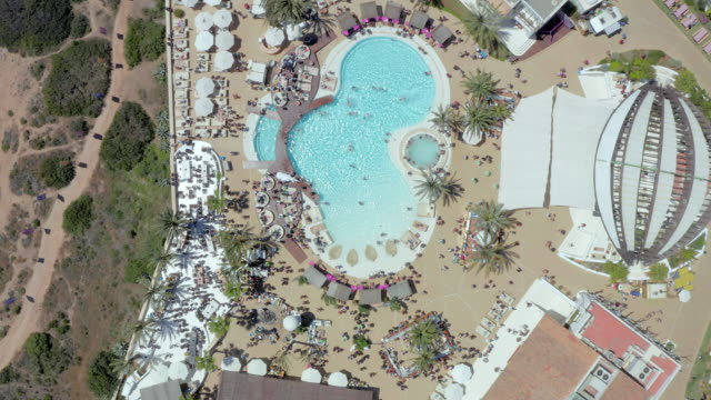 aerial: drone moving over people enjoying at tourist resort - ibiza, spain - イビサ島点の映像素材/bロール