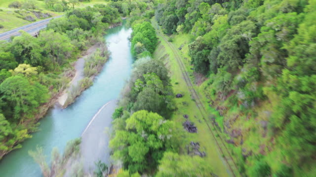 aerial: drone moving over river amidst highway and railway tracks in valley, scenic view of green trees and landscape against sky - napa valley, california - rail transportation stock videos & royalty-free footage