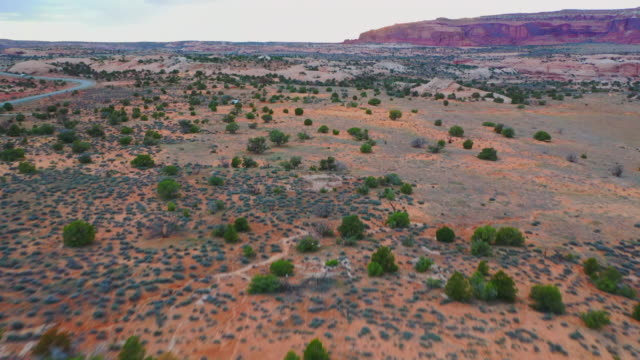 aerial: drone moving over rock formation approaching campsite in desert at canyonlands national park during sunset - canyonlands national park stock videos & royalty-free footage