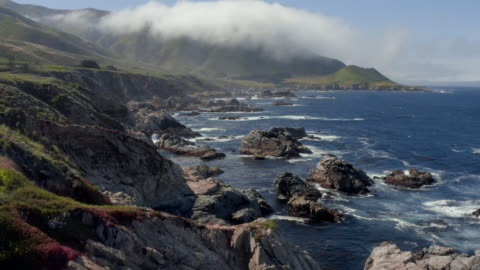 aerial: drone moving over rocks in sea by cliff against mountains - big sur, california - drone stock videos & royalty-free footage