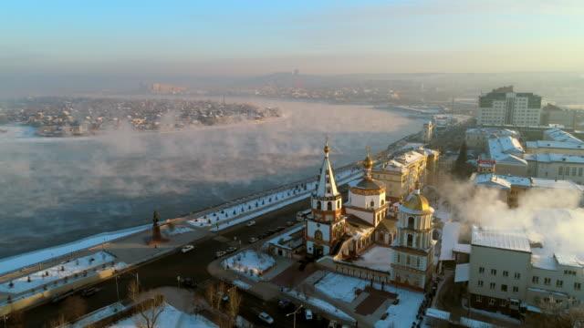 vidéos et rushes de aerial: drone moving over sobor bogoyavlensky by vehicles on street and snow covered promenade - irkutsk, russia - fédération de russie
