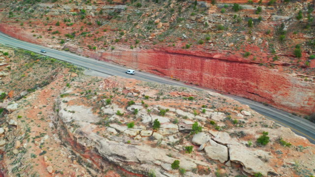 aerial: drone moving over van on winding road amidst rock formation at canyonlands national park - canyonlands national park stock videos & royalty-free footage