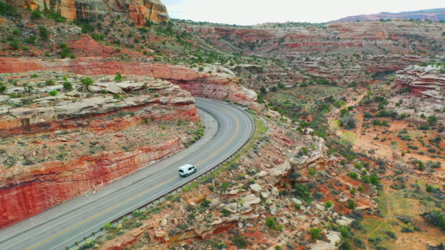 aerial: drone moving over van on winding road by rock formation at canyonlands national park - canyonlands national park stock videos & royalty-free footage