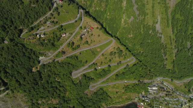 aerial: drone moving over vehicle traveling through zigzag highway on mountain during sunny day - geiranger fjord, norway - zigzag stock videos & royalty-free footage