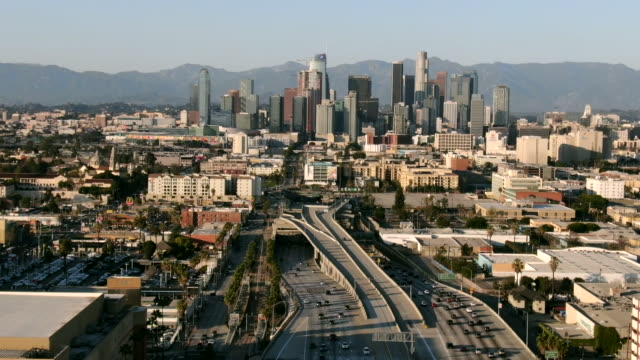 aerial: drone moving over vehicles on freeway amidst buildings in city against sky, cityscape against mountains - los angeles, california - city of los angeles bildbanksvideor och videomaterial från bakom kulisserna