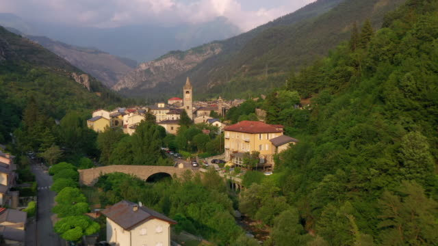 vidéos et rushes de aerial: drone moving towards houses and mountain range and trees - alpes-maritimes, france - france