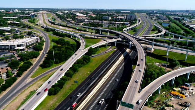 aerial drone moving towards huge interchange turnaround loops and highways change in autsin , texas - autostrada interstatale americana video stock e b–roll