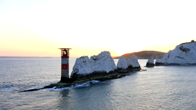 aerial drone needles uk lighthouse helipad sea sunrise - kreidefelsen stock-videos und b-roll-filmmaterial