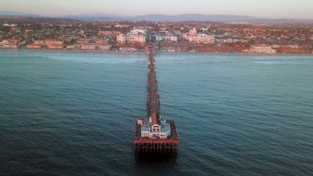 aerial drone: ocean pier and cityscape during sunset - oceanside stock videos and b-roll footage