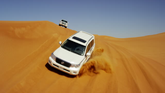 vidéos et rushes de aerial drone of 4x4 vehicles driving across dubai - dune de sable