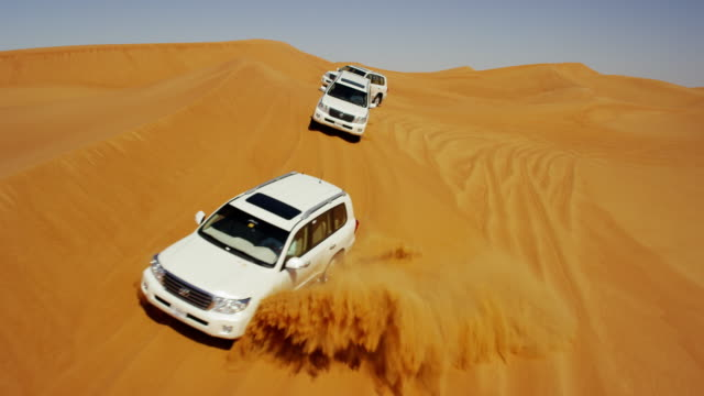 aerial drone of 4x4 vehicles driving across dubai - sand dune stock videos and b-roll footage