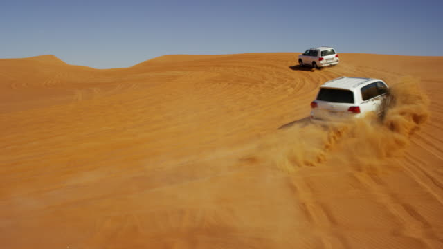 aerial drone of 4x4 vehicles driving across dubai - track imprint stock videos & royalty-free footage