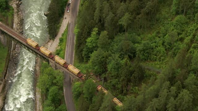 aerial drone of cargo train crossing bridge over river - cargo train stock videos & royalty-free footage