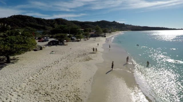 Aerial drone of people walking on the beach