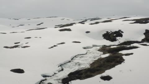 stockvideo's en b-roll-footage met luchtdrone buiten mening: bevroren berggebied in noorwegen - melting
