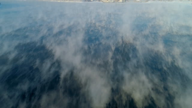 aerial: drone over fog covering angara river approaching cityscape - irkutsk, russia - covering stock videos & royalty-free footage