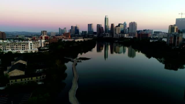 aerial drone over pedestrian bridge austin texas mirror image sunrise belt of venus colors - austin texas stock videos & royalty-free footage