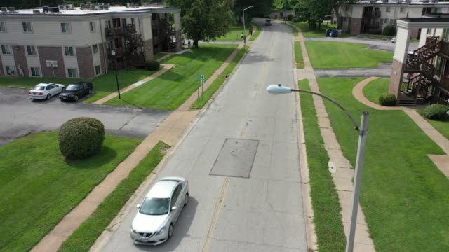 aerial drone over the location where michael brown was fatally shot on canfield drive in ferguson missouri - aerial or drone pov or scenics or nature or cityscape stock videos & royalty-free footage