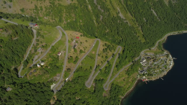 aerial: drone over zigzag winding road on green mountain by fjord during sunny day - geiranger fjord, norway - zigzag stock videos & royalty-free footage