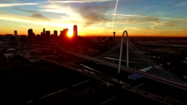 Aerial Drone Pan across Margaret Hunt Hill Bridge as sun passing across Downtown Skyline Cityscape