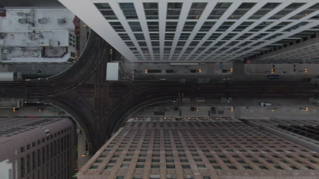 aerial: drone panning over elevated railway tracks over street amidst buildings in city - chicago, illinois - schwenk stock-videos und b-roll-filmmaterial