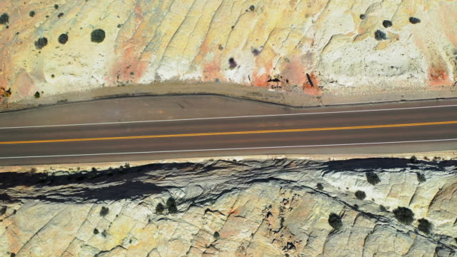 aerial: drone panning over empty highway on mountain at grand staircase-escalante national monument in desert - grand staircase escalante national monument stock-videos und b-roll-filmmaterial