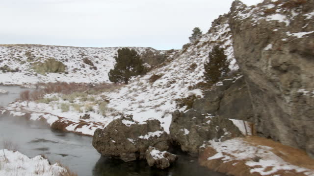 aerial: drone panning over hot creek geological site emitting steam amidst snow during winter - mammoth lakes, california - mammoth lakes video stock e b–roll