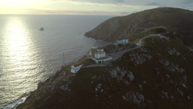 vídeos y material grabado en eventos de stock de aerial: drone panning over large building and cape finisterre lighthouse on rocky mountain during sunset - galicia