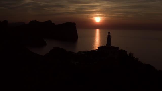 aerial: drone panning over silhouette lighthouse at cap de formentor on mountain by sea and against sky during sunset - mallorca, spain - バレアレス点の映像素材/bロール