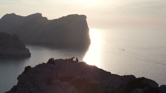 aerial: drone panning over silhouette people hiking while sitting on mountain peak by sea against sky during sunset - mallorca, spain - majorca stock videos & royalty-free footage