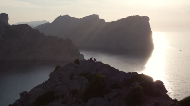 aerial: drone panning over silhouette people sitting on mountain peak by sea against sky during sunset - mallorca, spain - majorca stock videos & royalty-free footage