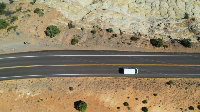 stockvideo's en b-roll-footage met aerial: drone panning over van moving on road at grand staircase-escalante national monument in desert - pan american highway