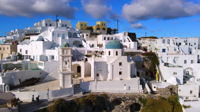 aerial: drone panning shot of famous anastasi orthodox church in city against sky on sunny day - santorini, greece - cyclades islands stock videos & royalty-free footage