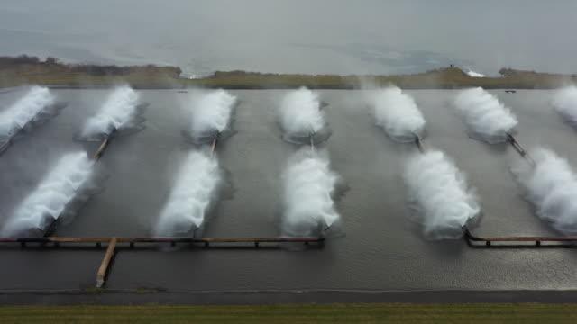 vidéos et rushes de vue panoramique de drone aérien de la centrale électrique et des fontaines industrielles sur des bassins de refroidissement. - rafraîchissement